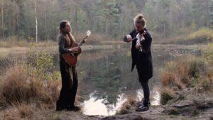 Afbeelding met Ilse Oversier met gitaar en een man met viool zingend bij het water